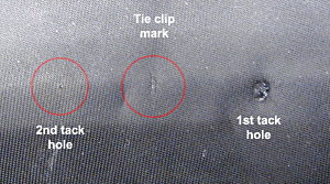 Fig. 3 Tie tack holes found on Coopers tie. Note permanent depression surrounding hole on right.