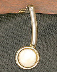 Fig. 1  Close-up of tie clip from black tie found on Cooper's seat.