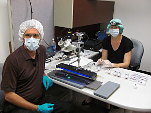 Fig. 1 Scientist Tom Kaye and Carol Abraczinskas use UV light (blue in photo) and a laser (green) to see stains and particles left on Cooper's tie for accurate sample collection. A forensic vacuum, with 0.8 micron filters, was used for high-density particle collection. FBI Archive - Seattle, WA 2011.